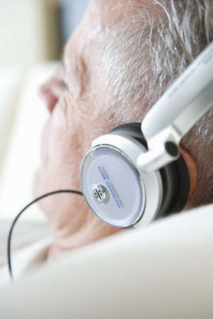 Senior man relaxing on sofa at home, listening to music on headphones, close-up, rear view