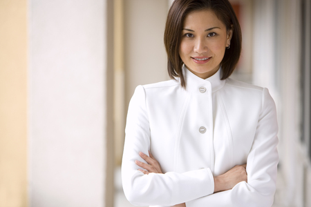 Businesswoman, with brown bobbed hair, wearing white business suit, arms folded, smiling, front view, portrait LANG_EVOIMAGES