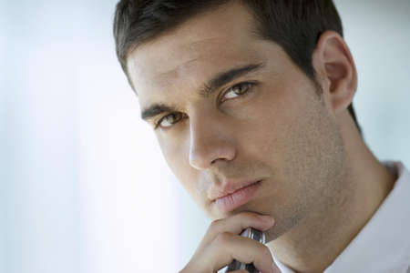 Businessman with hand on chin, thinking, close-up, portrait