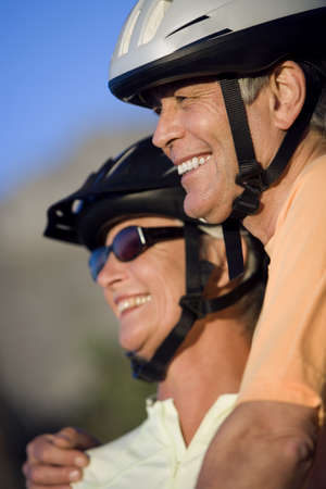 Mature couple, in cycling helmets, standing on mountain trail, looking at scenery, smiling, close-up LANG_EVOIMAGES