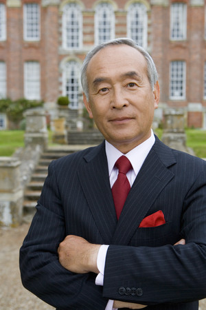Mature businessman with arms crossed in front of manor house, portrait, close-up LANG_EVOIMAGES