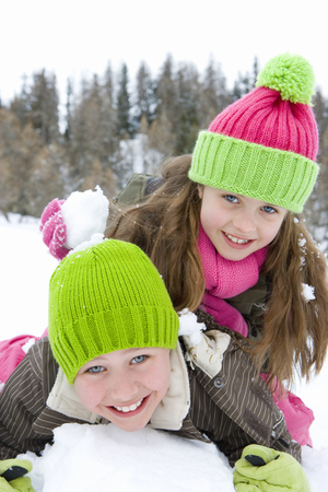 Brother and sister (6-8) wearing woolen hats, lying in snow, smiling, portrait, close-up