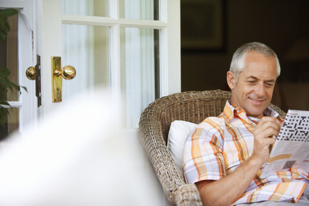 Mature man relaxing in wicker chair at home, doing newspaper crossword, smiling, focus on background LANG_EVOIMAGES