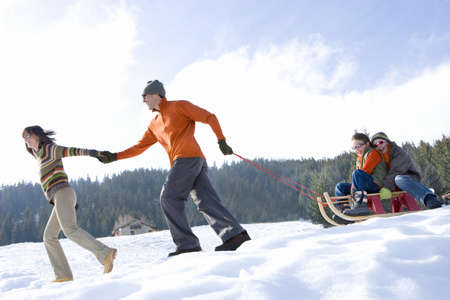 Couple pulling son and daughter (7-9) on sled in snow, smiling, side view LANG_EVOIMAGES
