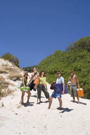 Group of teenagers (17-19) standing on sand dune at beach, portrait, low angle view