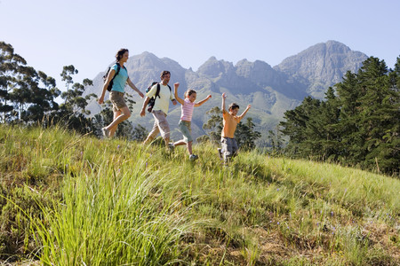 Family hiking on mountain trail, walking in line, boy (8-10) leading, side view LANG_EVOIMAGES