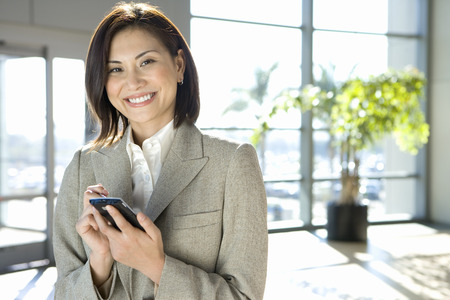 Businesswoman standing in airport, using personal electronic organiser, smiling, portrait LANG_EVOIMAGES