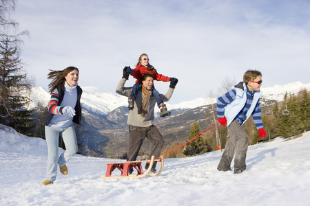 Boy pulling sled in snow field in front of parents and sister, mountain range in background
