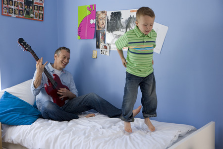 Father and son (2-4) in bedroom, boy jumping on bed, man playing electric guitar, smiling LANG_EVOIMAGES