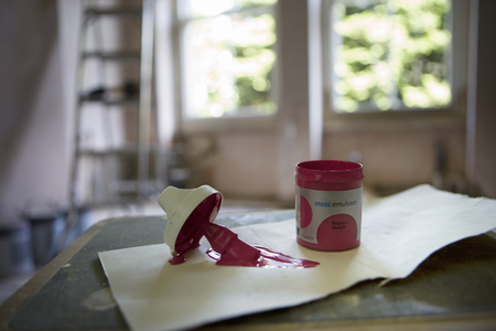 Small tin of pink paint and paintbrush on paper in undecorated room, close-up, focus on foreground LANG_EVOIMAGES