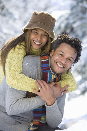 Portrait of mixed race couple hugging in snow LANG_EVOIMAGES