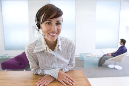 Businesswoman with headset, smiling, portrait LANG_EVOIMAGES