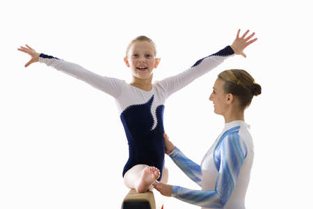 Young female gymnast (9-11) on balance beam with teacher, smiling, portrait