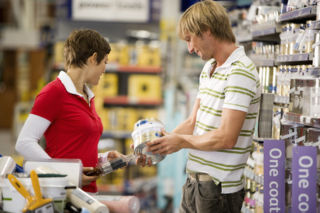 Couple shopping in DIY shop, man choosing tin of paint, side view LANG_EVOIMAGES