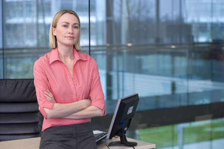 Blonde businesswoman, in pink blouse, leaning against desk in office, arms folded, portrait, window in background LANG_EVOIMAGES