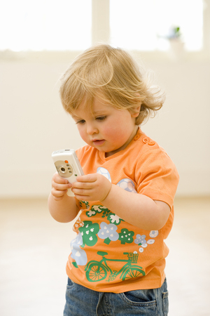 Male toddler (15-18 months) playing with mobile phone, close-up