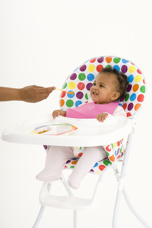 Mother feeding baby girl (3-6 months) in highchair LANG_EVOIMAGES