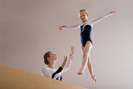 Gymnastics instructor teaching girl (5-7) on balance beam, low angle view