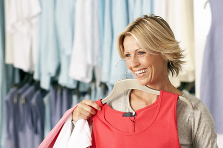 Blonde woman choosing red sleeveless top in clothes shop, smiling LANG_EVOIMAGES
