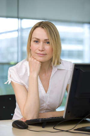 Businesswoman sitting at desk in office beside flat screen computer monitor, hand on chin, smiling, portrait