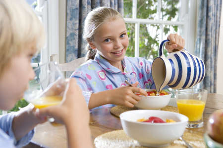 Brother and sister (6-10) at breakfast table, girl pouring milk, smiling, portrait (differential focus) LANG_EVOIMAGES