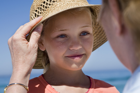 Senior woman placing straw sun hat on granddaughters head, girl (8-10) smiling (differential focus)