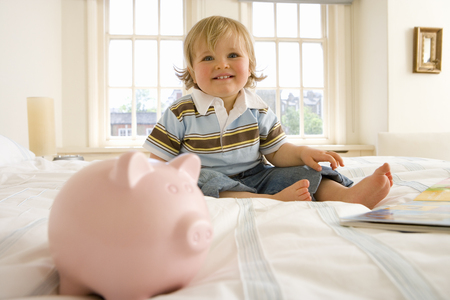 Baby boy (9-12 months) by piggy bank on bed, smiling
