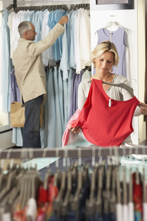Mature couple shopping in clothes shop, woman holding red top, man choosing top from clothes rail LANG_EVOIMAGES