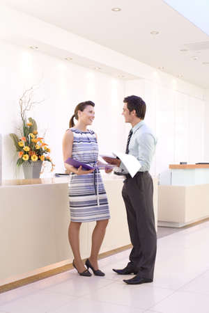 Businessman and woman with paperwork by reception, smiling at each other, side view LANG_EVOIMAGES