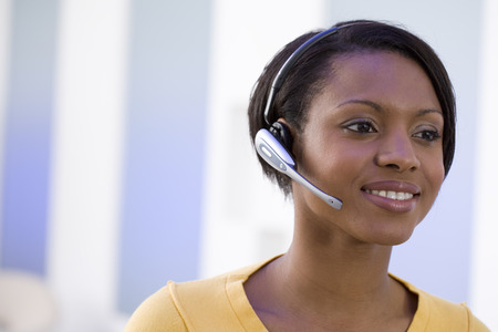 Woman in headset, smiling, close-up LANG_EVOIMAGES