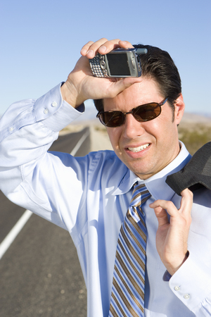 Businessman in sunglasses with mobile phone on side of road, hand to head, close-up