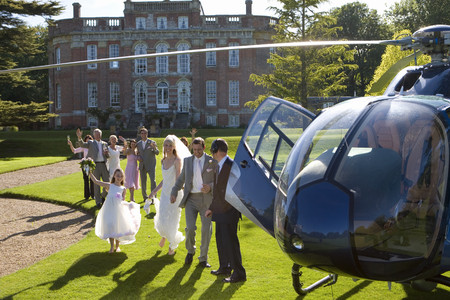 Wedding guests waving at bride and groom by helicopter LANG_EVOIMAGES