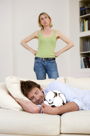 Young man on sofa with football, smiling with eyes closed, woman in background with hands on hips (differential focus) LANG_EVOIMAGES