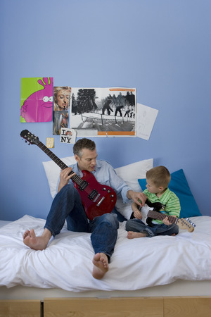 Father an son (2-4) on bed with electric guitars