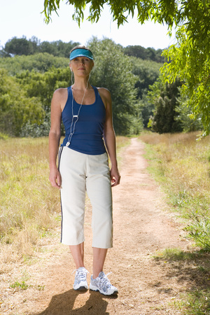 Woman in exercise clothes with earphones on country path, smiling, portrait