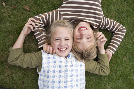 Boy and girl (8-11) lying cheek to cheek on grass, smiling, portrait, front view, overhead view