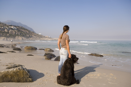 Woman with dog on beach, looking out to sea, rear view LANG_EVOIMAGES