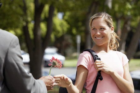 Woman receiving single pink flower from man, smiling