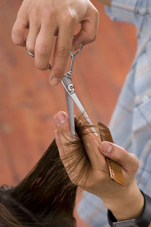 Hairdresser cutting hair, close-up