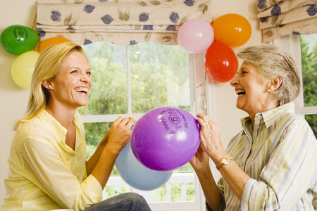 Senior woman and adult daughter preparing birthday party at home, inflating balloons, laughing, side view