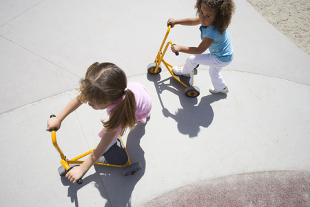 Girls (4-6) playing on tricycle scooters, elevated view