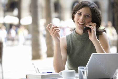 Businesswoman talking on cell phone in cafe