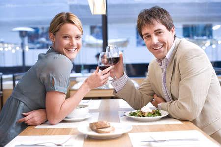 Couple proposing toast in restaurant, smiling, portrait