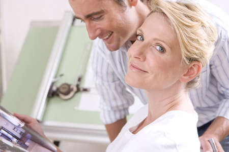 Couple by drafting board, portrait of woman smiling
