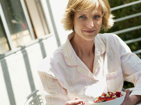 Woman sitting at balcony table, eating bowl of fresh strawberries, smiling, side view, close-up, portrait (tilt)