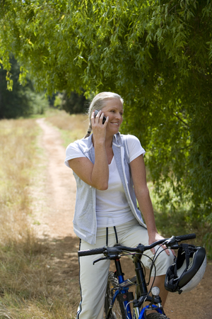 Woman on bicycle on country track, using mobile phone