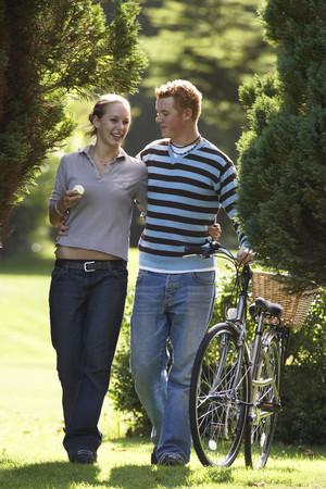 Young couple walking in park, man pushing bicycle, smiling