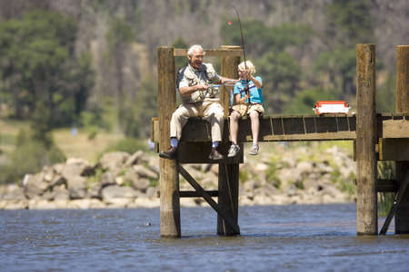 Boy (10-12) fishing with grandfather on jetty