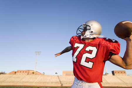 American football quarterback, in red strip, about to throw ball during competitive game, profile LANG_EVOIMAGES