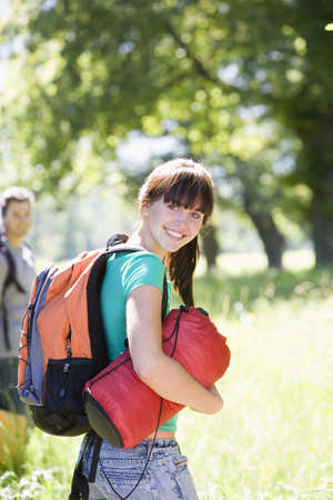 Young couple, with rucksacks, standing in woodland clearing, departing on hiking trip, woman carrying sleeping bag, smiling, portrait